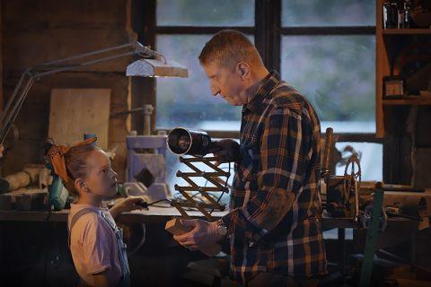 zdjęcie, dziadek pokazuje dziewczynce jak włącza się starą lampę