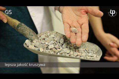 zdjęcie, łopatka z pokruszonym gruzem betonowym, na dłoni jeden kawałek gruzu.